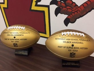 Astronaut High displays two golden Wilson footballs sent by the NFL to commemorate former War Eagles who played in Super Bowls, Cris Collinsworth and Wilber Marshall.